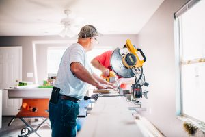 older man remodeling home with mitre saw